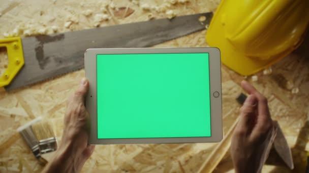 Držby tablet pc v režimu na šířku s tabulkou workshop s tesařské nářadí v pozadí