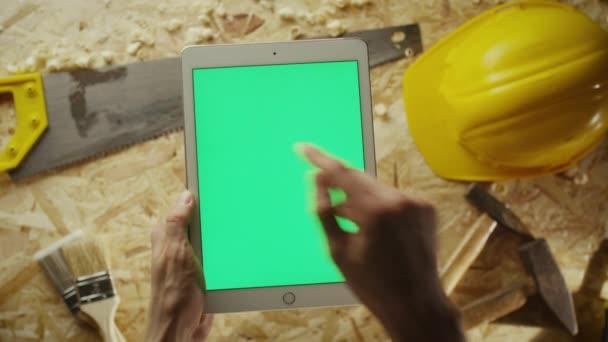 Držby tablet pc v režimu portrét s tabulkou workshop s tesařské nářadí v pozadí