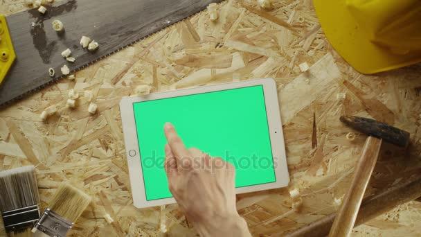 Použití počítače tablet pc v režimu na šířku na workshop stolu vedle tesařské nářadí