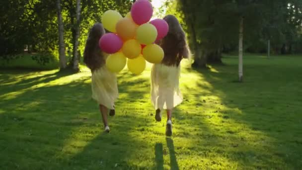 Twin Girls Is Running At Park With Balloons In Hands At Sunset Time Stock Footage
