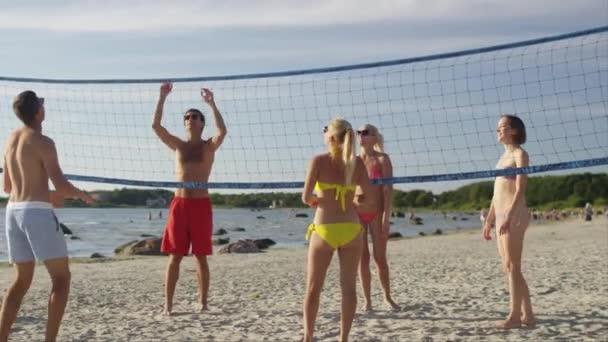 Skupina mladých lidí hrát volejbal na pláži