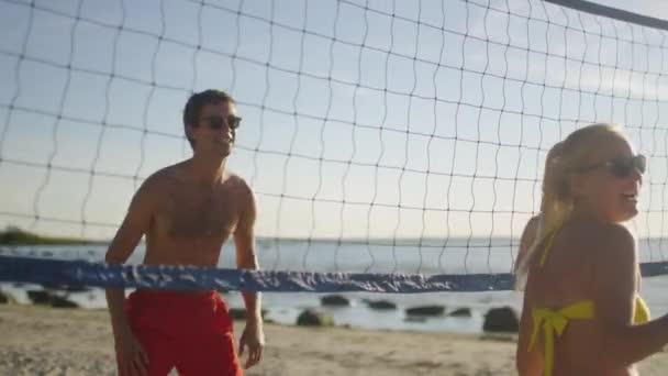Muž v sluneční brýle v plážový volejbal hraje s přáteli