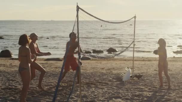 Skupina mladých lidí, kteří hrají v plážovém volejbalu v západu slunce světlo. Slow motion 60 Fps.