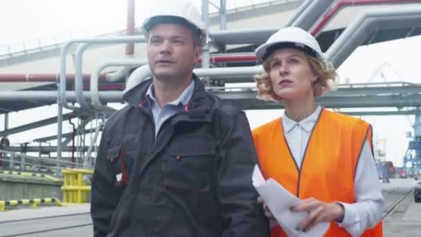 Arbeitnehmer in harte Hüte gehen und sprechen im industriellen Umfeld