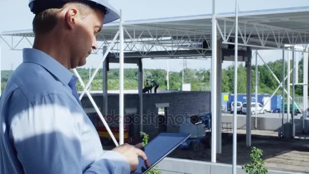 Inženýr v přilbu s Tablet Pc pro stavebnictví.