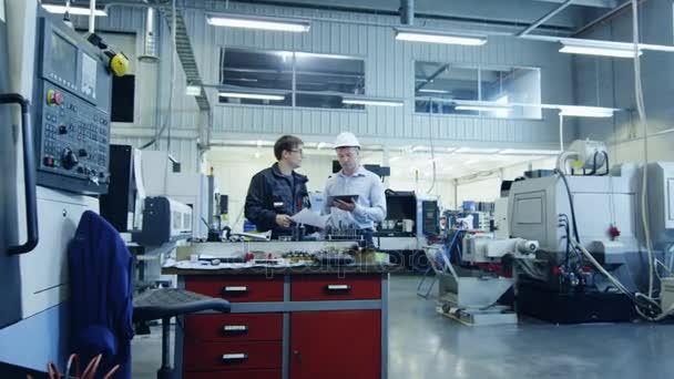 Inženýr přilbu a tovární dělník jsou hovořím o Blueprint