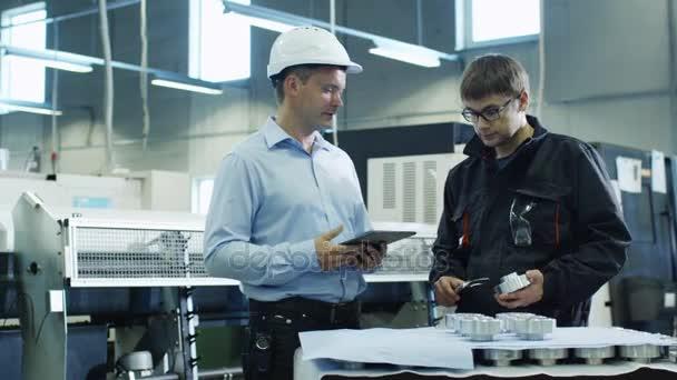 Inženýr přilbu a tovární dělník jsou kontroly kvality Detail na tovární
