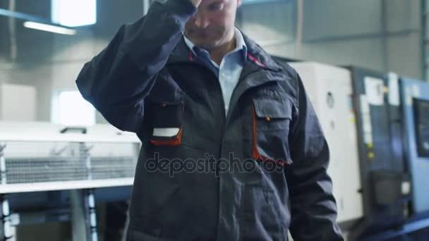 Fabrikarbeiter setzt Harthut und Schutzbrille auf