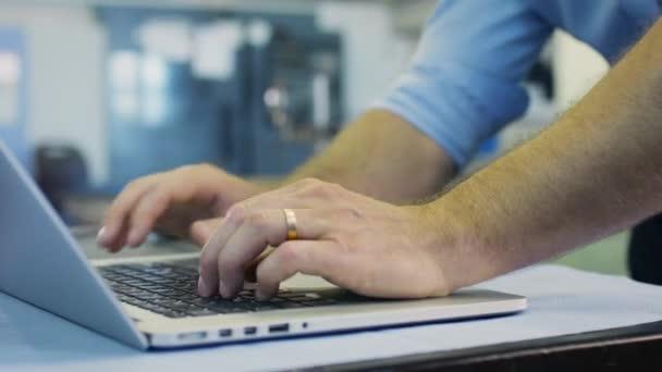 Inženýr je psaní na notebooku v průmyslovém prostředí
