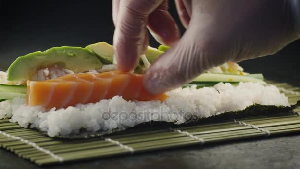 Professional Chef Preparing Sushi Rolls with Salmon and Avocado in Japanese Restaurant