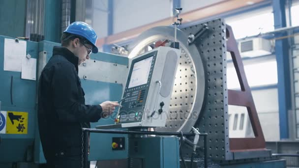 Factory worker is programming a CNC milling machine with a tablet computer.