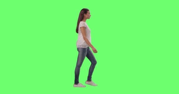 Casual giovane ragazza bruna sta camminando su un mock-up verde schermo sullo sfondo