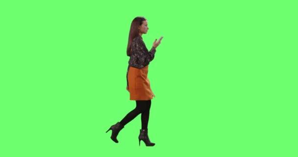 lässiges junges brünettes Mädchen läuft und spricht auf dem Smartphone auf einem grünen Bildschirm im Hintergrund.
