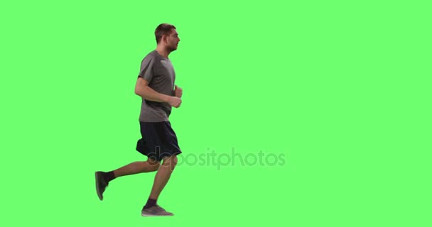 Man in a T-shirt is Jogging on a Mock-up Green Screen in the Background.
