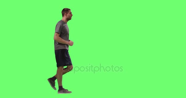 Man in a T-shirt is Sport Walking on a Mock-up Green Screen in the Background.