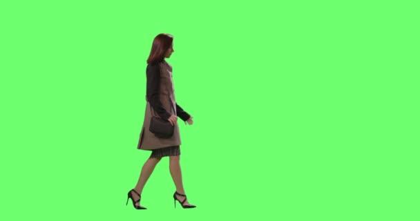 lässige brünette Frau läuft auf einer grünen Leinwand im Hintergrund.