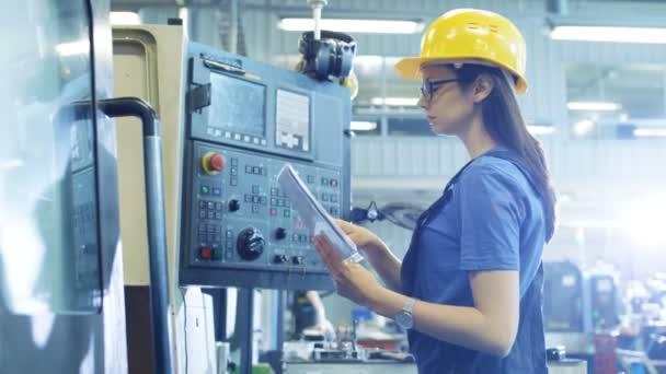 Profesionální žena operátor v Hard Hat nastavení nahoru / programování Cnc stroj s ovládacím panelem v velké průmyslové továrně