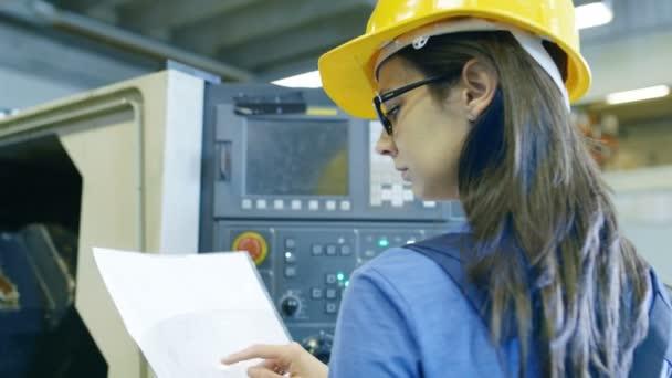 Profesionální žena operátor v Hard Hat nastavení nahoru / programování Cnc stroj s pomoci v Ovládacích panelech. Velké průmyslové továrně je viditelný