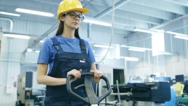 Krásné ženské pracovník v přilbu provozuje paletový vozík ve velké tovární budovy