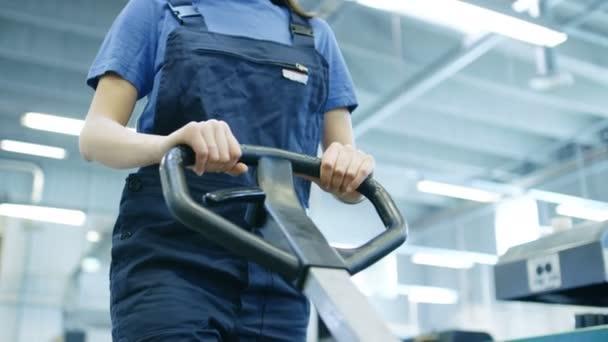 Krásné ženské pracovník v přilbu provozuje paletový vozík ve velké tovární budovy.