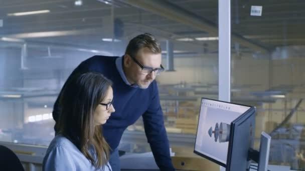 Ženské inženýr a vedoucí projektu muž práce na 3d turbína / motoru Model v její Cad softwaru. V továrně je vidět z okna kanceláře