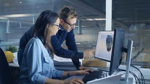 Ženské průmyslových techniků a Male hlavní inženýr navrhování 3d turbína / motoru Model s pomocí Cad softwaru. Pracují na počítači s dvěma displeji