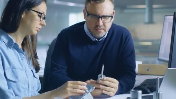 Männlich-Chief Engineer berät mit weiblichen Techniker über die Lebensdauer. Computer-Display zeigt 3d gestaltete Turbine / Motor Teil.