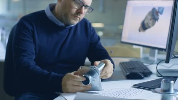 Cílené Male šéfinženýr kontroluje komponenty trvanlivost. Průmyslový Design Software je otevřený v počítači jeho stůl. Je vidět v pozadí velké továrně