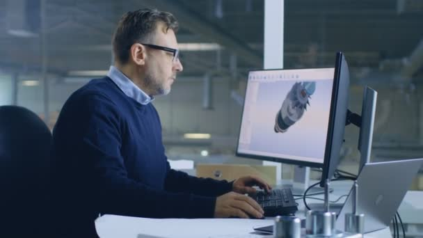 Starší muž inženýr pracuje na 3d turbína / motoru Design na jeho osobním počítači s pomocí Cad softwaru. V pozadí vidíme velké továrny