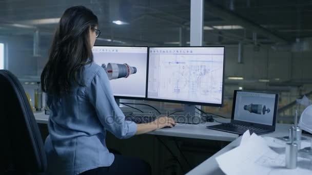 Chefkonstrukteurin entwirft ein 3D-Modell einer Turbine oder eines Triebwerksteils. Der zweite Monitor zeigt technische Baupläne. Aus dem Bürofenster sieht man eine große Fabrik.