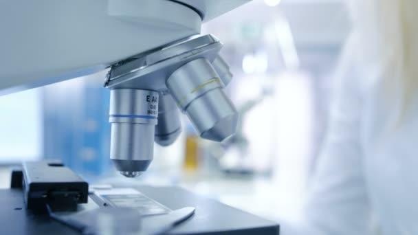 Zár-megjelöl szemcsésedik-ból egy orvosi kutató látszó-ba Mikroszkóp. Laboratóriumi Modern és világos.