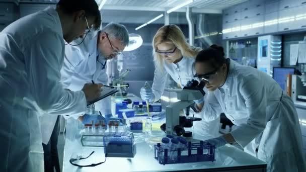 Orvosi kutatás tudósok egy új generációs kísérleti gyógyszeres kezelés együttesen dolgozik a csapat. Laboratóriumi néz elfoglalt, világos és Modern.
