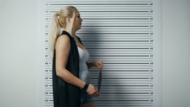 In a Police Station Arrested Woman Steps in and Gets Side, Front-View Mug Shot. She Wears Saucy Clothes, Has Heavy Makeup and Holds Placard. Height Chart in the Background.