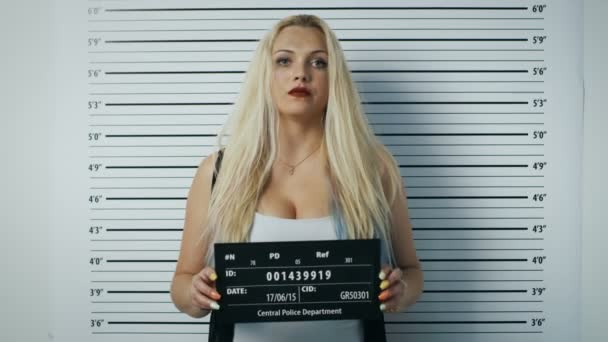 In a Police Station Arrested Woman Posing for Side, Front-View Mugshot. She Chews Gum, Wears Saucy Clothes, Has Smudged Heavy Makeup, Her Hair Is Disheveled and SHe Holds Placard. Height Chart in the Background.