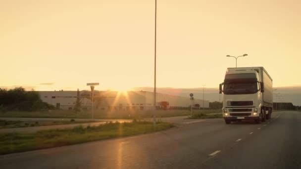 Přední kamera sleduje semi-Truck s nákladní přívěs jízda na dálnici. On je prolétla oblast průmyslového skladu s západ slunce v pozadí