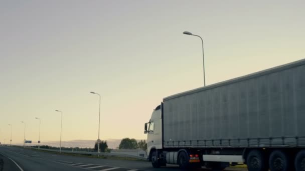Semi-Truck with Cargo Trailer Drives on a Highway. Static Camera Follows Him. In the Background Rural Area with Rising Sun.