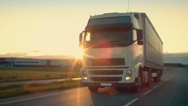 Přední kamera sleduje semi-Truck s nákladní přívěs jízda na dálnici. On je prolétla oblast průmyslového skladu s západ slunce v pozadí.