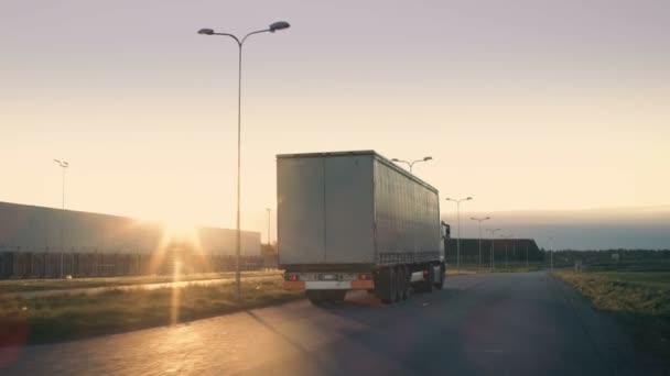 Nachschuss eines Sattelzugs mit Ladeanhänger, der sich auf einer Autobahn bewegt. weißer LKW fährt auf leerer Straße durch Industriegebiet, im Hintergrund scheint die Sonne.
