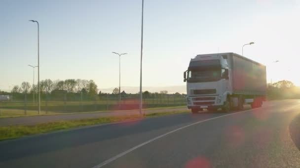 Semi-Truck with Cargo Trailer Moving on a Highway. White Truck Transports Freight Through Industrial Warehouse Area.
