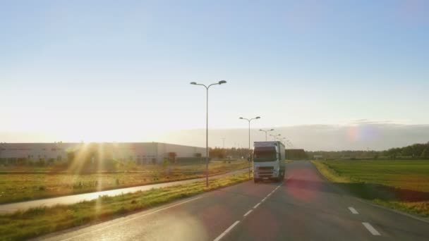 White Semi Truck with Cargo Trailer Drives on a Highway with Beautiful Sunny Scenery in the Background.