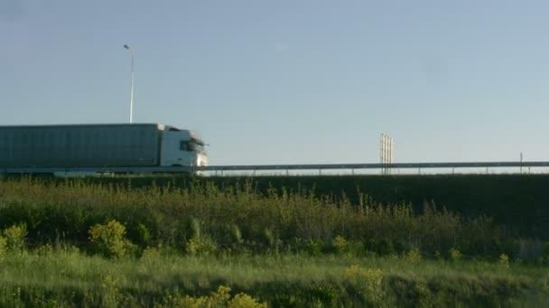 Boční pohled bílé Semi Truck s nákladní přívěs jízda přes most. Nádherné scenérie se vozidlo pohybuje na nadjezd, zatímco svítí slunce.