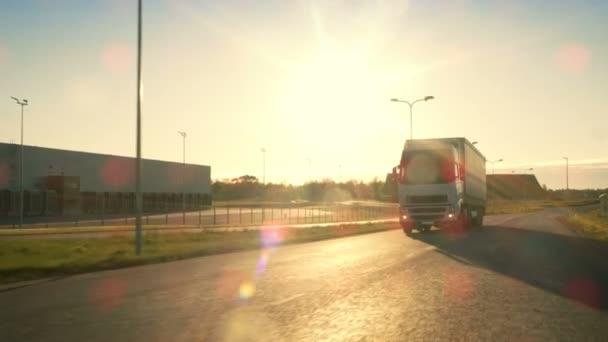 Přední kamera sleduje Semi Truck s nákladní přívěs jízda na dálnici. On je prolétla oblast průmyslového skladu s západ slunce v pozadí