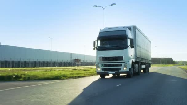 Front-View Camera Follows Semi Truck with Cargo Trailer Driving on a Highway. Hes Speeding Through Industrial Warehouse Area while Sun Shines and no other Vehicles are on the Road.