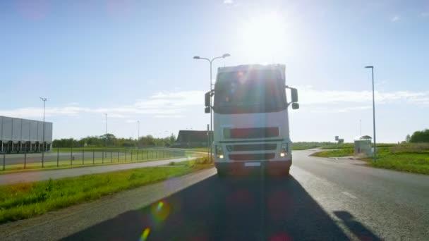 Großer weißer Sattelschlepper mit Ladeanhänger bewegt sich auf der leeren Straße im Industriegebiet, im Hintergrund scheint die Sonne.