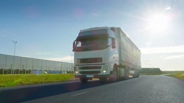 Velké bílé Semi Truck s nákladní přívěs pohybuje na prázdné silnici průmyslové oblasti s slunce zářící na pozadí.