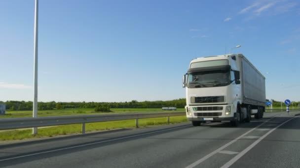 Velké bílé Semi Truck s přívěs nákladní disky na prázdné silnici průmyslové oblasti s slunce zářící na pozadí