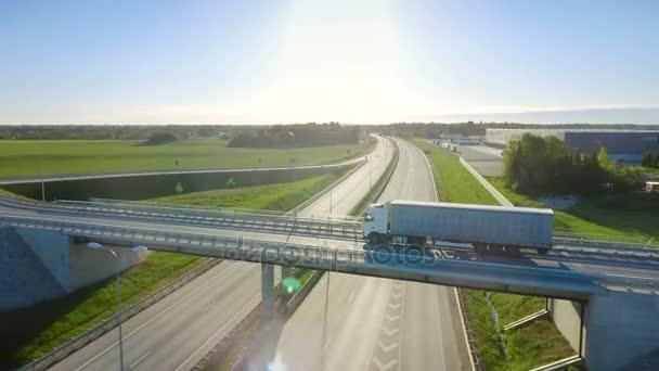 Letecký pohled na bílé Semi Truck s nákladní přívěs předávání dálniční nadjezd / most. 18 Wheeler je nový, načítání sklady jsou vidět v pozadí