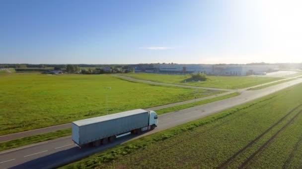 Letecký pohled na bílé Semi Truck s poplatky na dálnici. V pozadí sklady a venkovské oblasti slunce svítí.