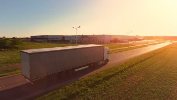 Luftaufnahme eines weißen Sattelzugs mit Ladeanhänger, der sich auf der Autobahn bewegt. Im Hintergrund sind Lagerhallen und industrielle Ladegebäude zu sehen. Sonnenuntergang.