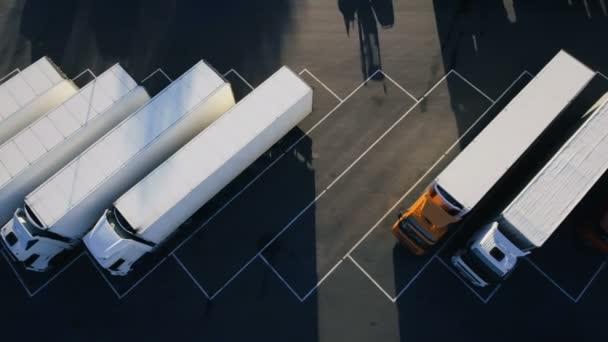 Pohybující se vzdušný Top View z zaparkoval Semi kamiony s nákladem / chladírenské návěsy stojící na vyhrazené parkovací místa